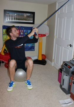 Downward chop with resistance band while sitting on exercise ball